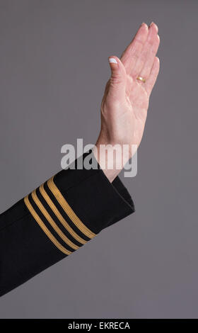 Airline officer in uniform making a gesture with her hand - Stock Photo