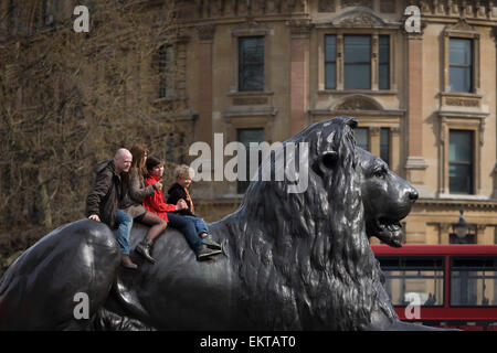 Tourist family sit on one of one of the four lions designed by Landseer at the base of Nelson's Column in Trafalgar - Stock Photo