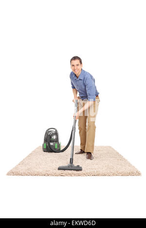 Full length portrait of a cheerful young man cleaning with a vacuum cleaner and looking at the camera - Stock Photo