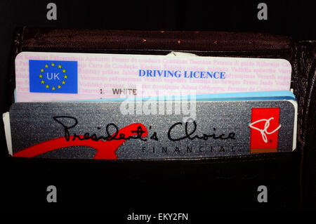 A UK driving license and a bank card inside a leather wallet. - Stock Photo