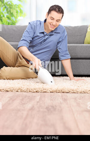Vertical shot of a young man holding a handheld vacuum cleaner and cleaning a carpet at home - Stock Photo