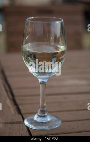 Glass of white Pinot Grigio Wine on a wooden table, in and English Pub, Leicester, England - Stock Photo