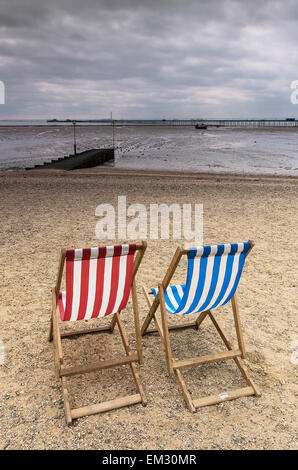Two empty deckchairs on Jubilee Beach in Southend on a cloudy day. - Stock Photo