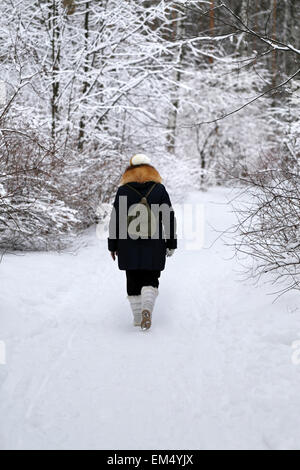 woman walks down a snowy path in winter forest - Stock Photo