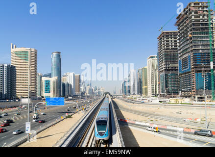 Metro train and skyline of Dubai at Jumeirah Lakes Towers (JLT)  in Dubai United Arab Emirates - Stock Photo