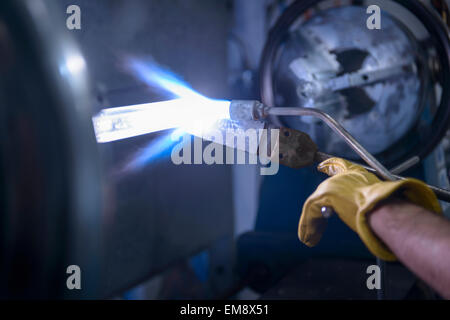 Industrial glass blower forming glass tube on lathe, close up - Stock Photo