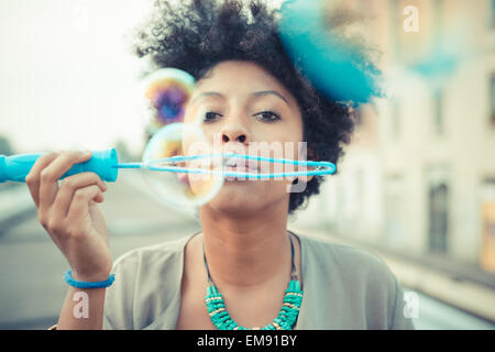 Portrait of young woman blowing bubbles with large wand - Stock Photo