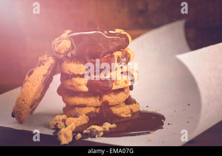 Chocolate sauce pouring over a stack of chocolate chip cookies on white curling baking paper against a dark wood - Stock Photo
