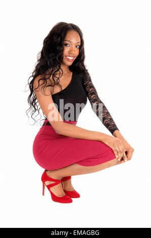 A lovely African American woman in a red skirt and black blouse crouching on the floor, smiling, isolated for white - Stock Photo