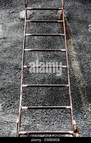 It's a photo of a rusted ladder in steel against a cement wall. It's symmetrical. there is nobody. - Stock Photo