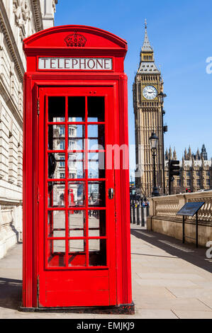 An iconic red Telephone Box with Big Ben in the background in London. - Stock Photo