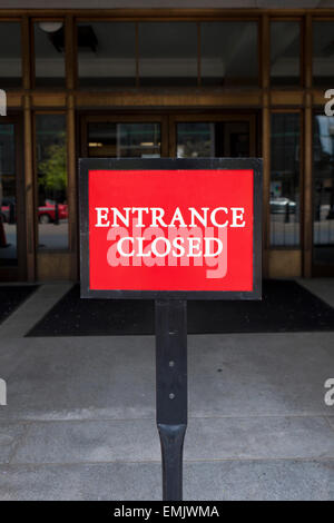 Entrance closed sign in front of building doors - USA - Stock Photo