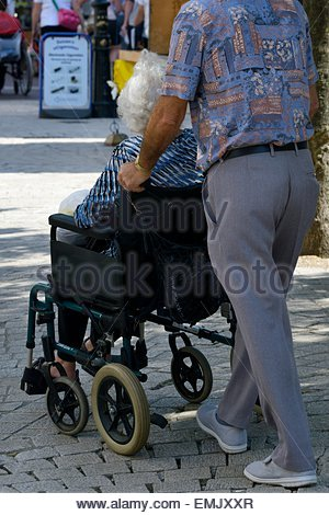 A man pushing an older woman in a wheelchair - Stock Photo