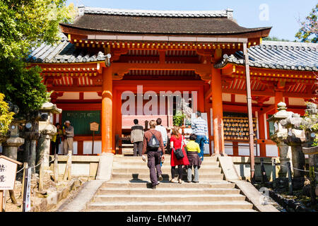 Japan, Nara, Kasuga Taisha Shrine. People, tourists walking up steps to the gateway, mon, of the shrine. - Stock Photo