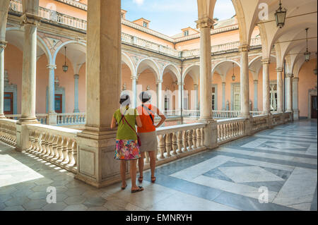 Genoa museum, two women visiting the Palazzo Tursi in Genoa pause to look down into the museum's courtyard, Genova, - Stock Photo