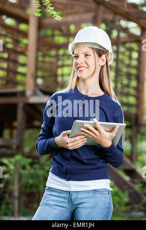 Smiling Female Architect Holding Digital Tablet At Site - Stock Photo