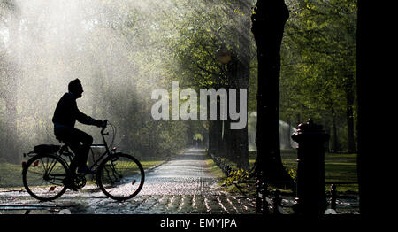 Berlin, Germany. 24th Apr, 2015. A man rides on his bicycle passing water sprinklers in the Tiergarten Park in Berlin, - Stock Photo