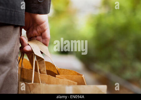 consumer basket, close up of paper shopping bags in male hand - Stock Photo