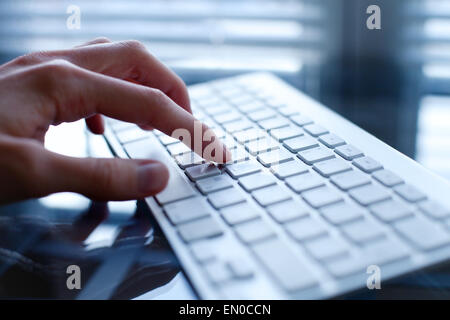 working on computer, close up of hand on keyboard - Stock Photo