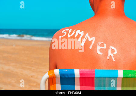 the word summer written with sunblock on the sunburnt back of a man who is sunbathing on the beach - Stock Photo