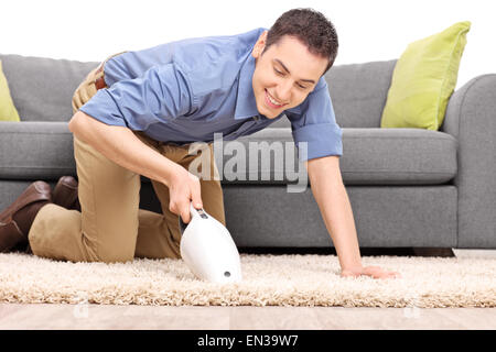 Young joyful man vacuuming a carpet with a handheld vacuum cleaner isolated on white background - Stock Photo