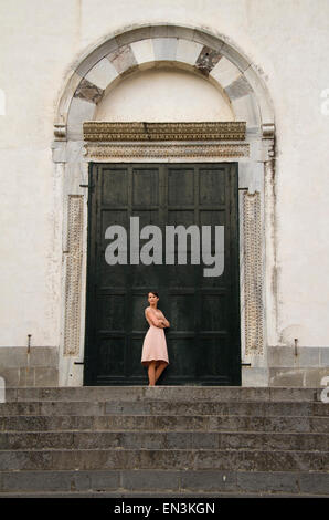 Italy, Ravello, Woman standing in front of closed doors - Stock Photo