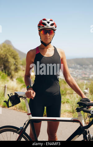Portrait of confident female triathlete standing with her bicycle on country road. Fitness woman in sportswear standing. - Stock Photo