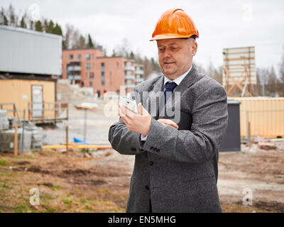 Male engineer uses cell phone, he wearing the suit and the hard hat, house construction site on background - Stock Photo