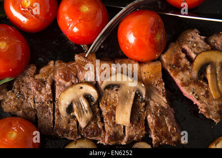 Grilling Strip Loin Steak in Cast Iron Frying Pan: Steak  is cooked  and sliced  - shown with grilled tomatoes and - Stock Photo