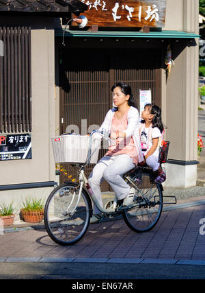 It's common to see two people riding a single bicycle in Japan - especially mothers & young children. Japanese mother - Stock Photo