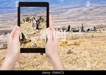 travel concept - tourist takes picture of standing menhirs of Zorats Karer (Carahunge) - pre-history megalithic - Stock Photo