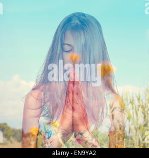 double exposure of a young brunette woman meditating and a peaceful landscape with yellow flowers - Stock Photo