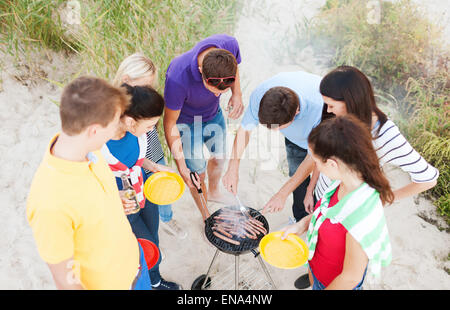 group of friends having picnic and making barbecue - Stock Photo