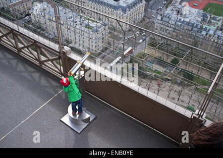 A child looks through a telescope on the Eiffel Tower - Stock Photo