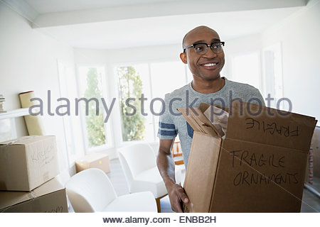 Smiling man carrying fragile moving box - Stock Photo