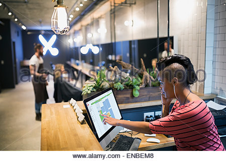 Hipster hairstylist working front desk computer hair salon - Stock Photo