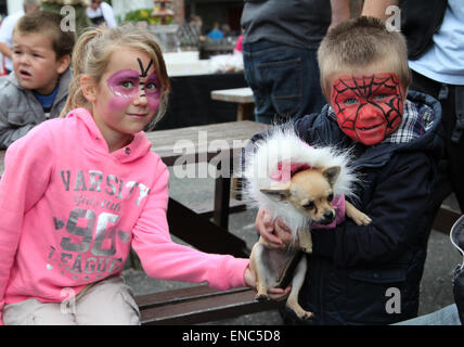 Children with painted faces and little dog dressed up at the International Puppet Festival in Witham, Essex - Stock Photo