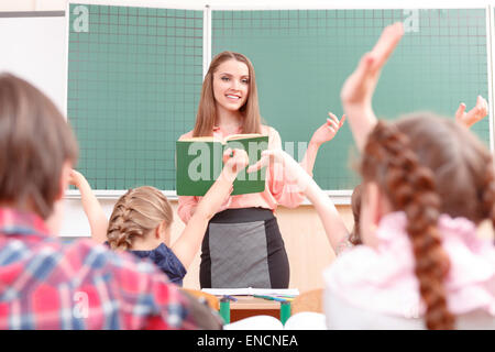 Pupils raising their hands during classes - Stock Photo