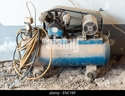 Old air compressor for small garage in the countryside. - Stock Photo