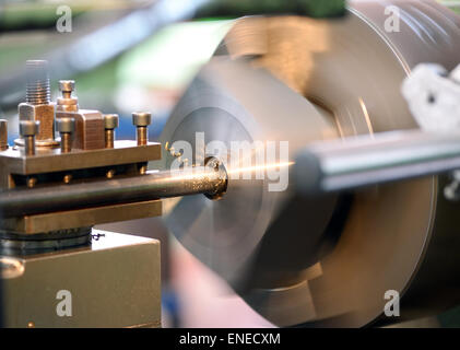 Close Up of Lathe in Operation with Focus on Spindle and Spinning Headstock and Gold Colored Shavings - Stock Photo