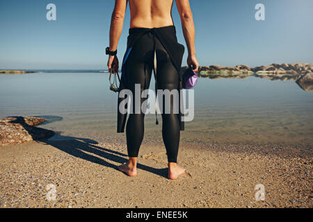 Rear view of young man standing on lake wearing wetsuit. Cropped shot of a triathlete preparing for a race wearing - Stock Photo