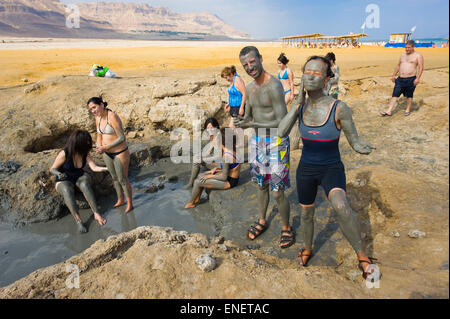 DEAD SEA, ISRAEL - OCT 13, 2014: People rub with mud on the beach of the dead sea in Israel - Stock Photo
