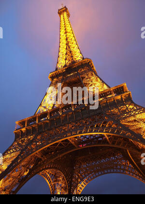 The Eiffel tower in Paris, France, illuminated with the top in the clouds mist fog - Stock Photo