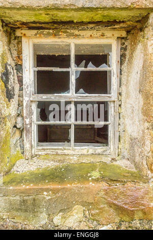 A window of a croft revealing a bedroom left as it was on the day it was damaged - Stock Photo