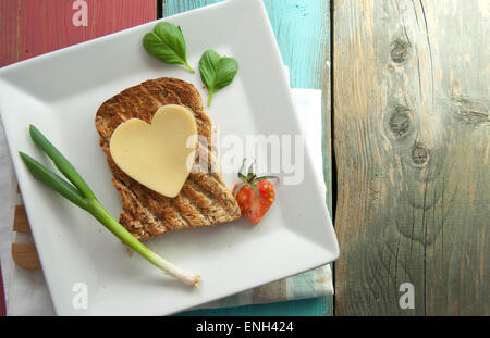 Heart shape slice of cheese on toasted whole grain bread - Stock Photo