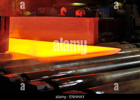 hot steel plate on conveyor inside of plant - Stock Photo
