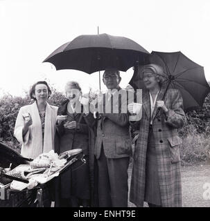 1950s, small group of mature adults roadside enjoying a picnic from the back of a car in the rain. - Stock Photo