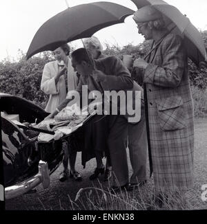 1950s, small group of mature adults roadside enjoy a picnic from the back or boot of their car in the rain. - Stock Photo