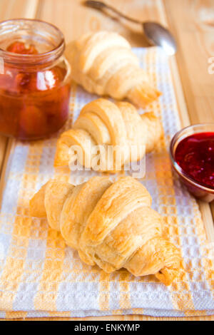 Homemade fresh croissants with jam (marmalade) on napkin and wooden table - Stock Photo