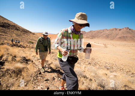 Africa, Namibia. Tok Tokkie Trails. Woman rehydrating. - Stock Photo